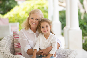 Older woman and granddaughter smiling on porchの写真素材 [FYI02152909]