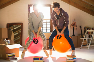 Couple jumping on exercise balls togetherの写真素材 [FYI02152921]
