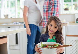 Girl holding bowl of salad in kitchenの写真素材 [FYI02153009]