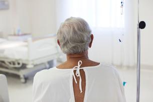 Older patient wearing gown in hospital roomの写真素材 [FYI02153069]
