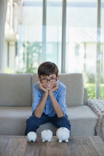 Boy examining piggy banks on coffee tableの写真素材 [FYI02153073]