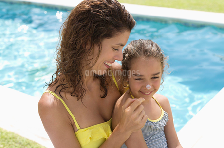 Mother applying sunscreen to daughter's noseの写真素材 [FYI02153193]