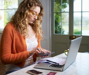 Woman paying bills on laptopの写真素材 [FYI02153200]