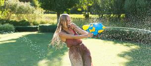Girl playing with water gun in backyardの写真素材 [FYI02153241]