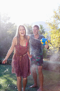 Couple playing with water guns in backyardの写真素材 [FYI02153246]