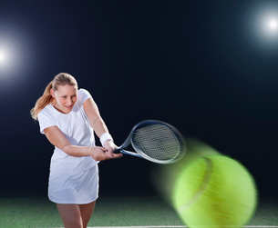 Tennis player hitting ball on courtの写真素材 [FYI02153262]