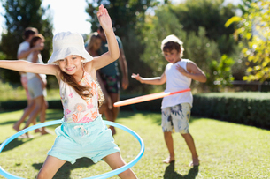 Children hula hooping in backyardの写真素材 [FYI02153316]