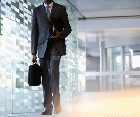 Businessman carrying briefcase in lobbyの写真素材 [FYI02153434]