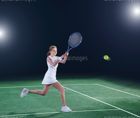 Tennis player hitting ball on courtの写真素材 [FYI02153496]