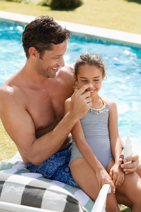 Father applying sunscreen to daughter's nose by swimming pooの写真素材 [FYI02153501]