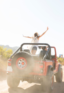 Woman cheering in sport utility vehicle on dirt roadの写真素材 [FYI02153527]