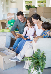 Family looking at picture frame on sofa among cardboard boxeの写真素材 [FYI02153587]