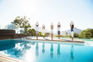 People practicing yoga at poolsideの写真素材 [FYI02153589]