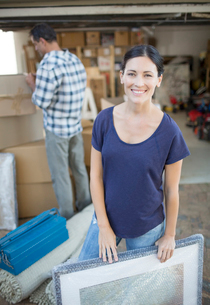 Woman holding picture in driveway among cardboard boxesの写真素材 [FYI02153621]