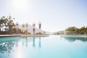 People practicing yoga at poolsideの写真素材 [FYI02153626]
