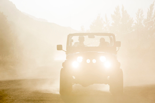 Sport utility vehicle driving on dirt roadの写真素材 [FYI02153642]