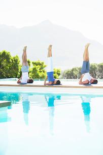 Men and woman practicing yoga poolsideの写真素材 [FYI02153651]