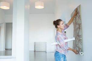 Woman hanging wallpaper in new houseの写真素材 [FYI02153660]
