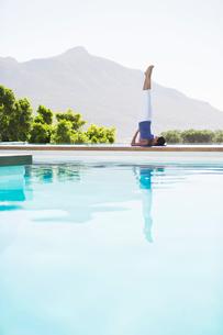 Woman practicing yoga at poolsideの写真素材 [FYI02153686]