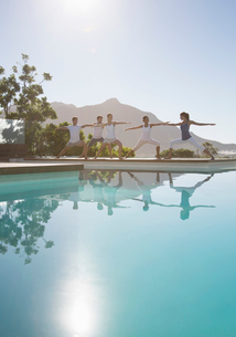 People practicing yoga at poolsideの写真素材 [FYI02153695]