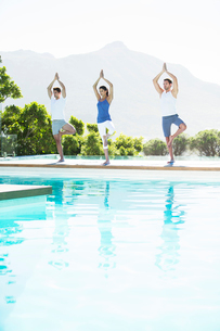 Men and woman practicing yoga at poolsideの写真素材 [FYI02153704]