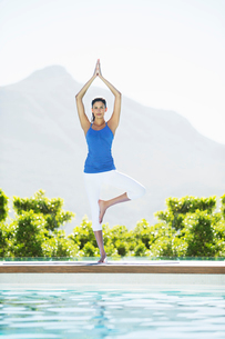 Woman practicing yoga at poolsideの写真素材 [FYI02153707]