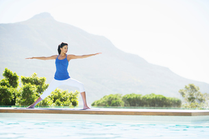 Woman practicing yoga at poolsideの写真素材 [FYI02153726]