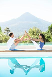 Couple practicing yoga poolsideの写真素材 [FYI02153733]