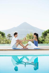 Couple practicing yoga poolsideの写真素材 [FYI02153740]