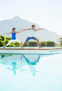 Couple practicing yoga at poolsideの写真素材 [FYI02153741]