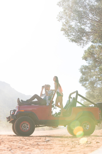 Couple relaxing in sport utility vehicle on dirt roadの写真素材 [FYI02153754]