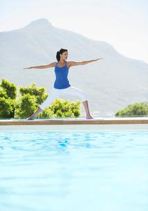 Woman practicing yoga at poolsideの写真素材 [FYI02153795]