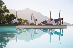People practicing yoga at poolsideの写真素材 [FYI02153801]