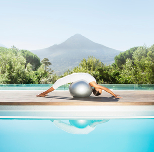 Woman stretching over fitness ball at poolsideの写真素材 [FYI02153817]