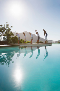 People practicing yoga at poolsideの写真素材 [FYI02153832]