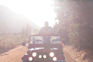 Man standing in sport utility vehicle on dirt roadの写真素材 [FYI02153845]