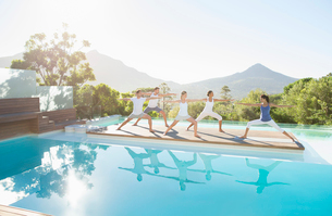 People practicing yoga at poolsideの写真素材 [FYI02153879]