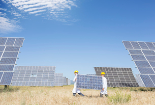 Scientists carrying solar panel in rural landscapeの写真素材 [FYI02153929]