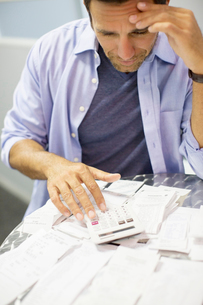 Frustrated man paying billsの写真素材 [FYI02153945]