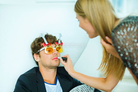 Woman applying lipstick to sleeping man at partyの写真素材 [FYI02153972]