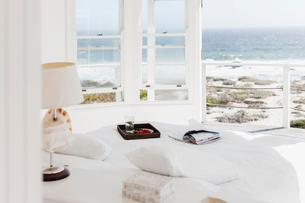 Breakfast tray and magazine on bed overlooking oceanの写真素材 [FYI02153988]