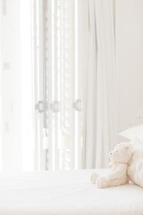 Teddy bear on white bedの写真素材 [FYI02154028]