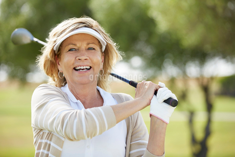 Senior woman playing golf on courseの写真素材 [FYI02154087]