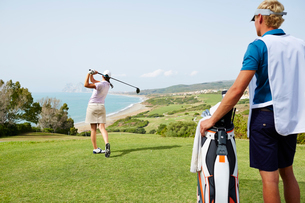 Caddy watching woman tee off on golf course overlooking oceaの写真素材 [FYI02154109]