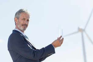 Businessman with glass of water by wind turbineの写真素材 [FYI02154122]
