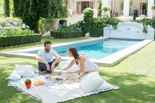 Couple enjoying picnic by poolの写真素材 [FYI02154134]