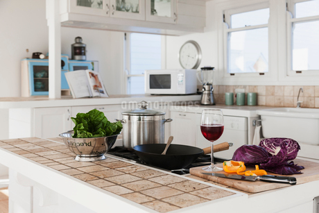 Vegetables and glass of red wine in kitchenの写真素材 [FYI02154145]