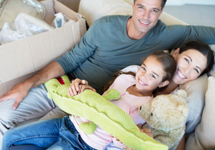 Portrait of smiling family with stuffed animals on sofaの写真素材 [FYI02154190]