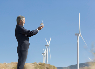 Businessman with glass of water by wind turbines in rural laの写真素材 [FYI02154205]