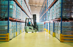Worker moving pallets with forklift in warehouseの写真素材 [FYI02154327]